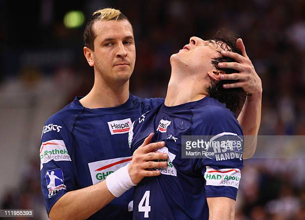 Pascal Hens of Hamburg comforts team mate Domagoj Duvnjak after the Toyota Handball Bundesliga match between HSV Hamburg and TV Grosswallstadt at the...