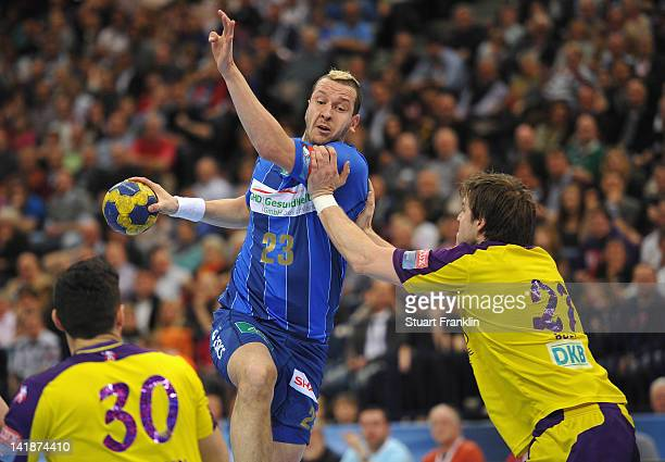 Pascal Hens of Hamburg is challenged by Ivan Nincevic and Alexander Pettersson of Berlin during the EHF Champions League match between HSV Hamburg...