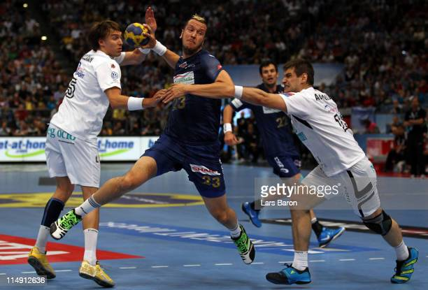 Pascal Hens of Hamburg is challenged by Jonas Kaellmann and Julen Aguinagalde of Ciudad Real during the EHF Final Four semi final match between...