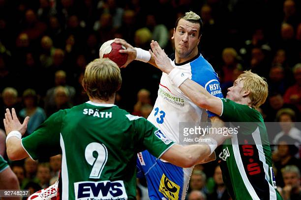 Pascal Hens of Hamburg is challenged by Manuel Spaeth and Christian Schoene of Goeppingen during the Toyota Handball Bundesliga match between FA...