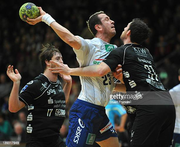 Pascal Hens of Hamburg is challenged by Nicolas Ivakno and Norman Floedl of Hildesheim during the Toyota Bundesliga match between Eintracht...