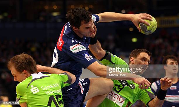 Pascal Hens of Hamburg is challenged by Piotr Przybecki of Hannover-Burgdorf during the Toyota Handball Bundesliga match between HSV Hamburg and...