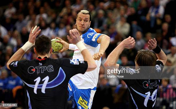 Pascal Hens of Hamburg tries to score over Maciej Dmytruszynski and Kristian Nippes of Dormagen during the Bundesliga match between HSV Hamburg and...
