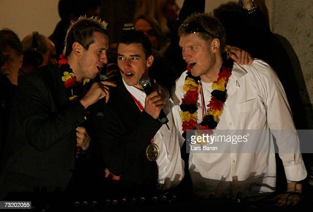 Pascal Hens sings with team mates Dominik Klein and Johannes Bitter on the balcony during the reception of the Mens German National Handball Team at...