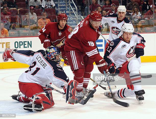Pascal Leclaire of the Columbus Blue Jackets and Mike Commodore of the Columbus Blue Jackets stop Shane Doan of the Phoenix Coyotes from scoring...