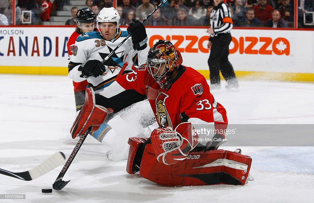 Pascal Leclaire #33 of the Ottawa Senators tries to control a rebound while Logan Couture #39 of the San Jose Sharks skates hard into the crease in a game at Scotiabank Place on December 2, 2010 in Ottawa, Ontario, Canada.