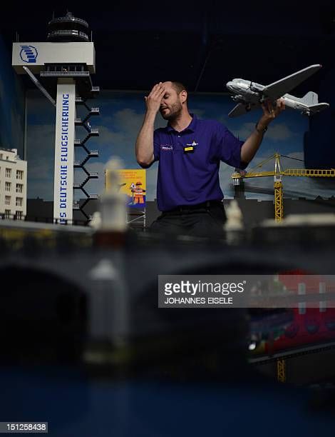 Pascal Lenhard employee of the Legoland Discovery Centre poses as he celebrates the opening of the miniature BerlinBrandenburg International airport...