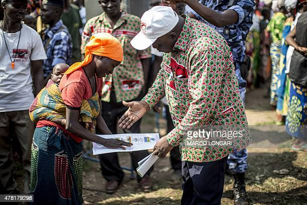Pascal Nyabenda president of the Burundian government party CNDDFDD explains how to vote to woman at a rally in Rubiza on June 23 2015 Parliamentary...