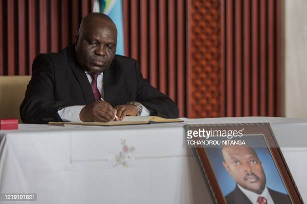 Pascal Nyabenda the President of National Assembly of Burundi signs in the book of condolences at the state house as Burundi mourns the death of...
