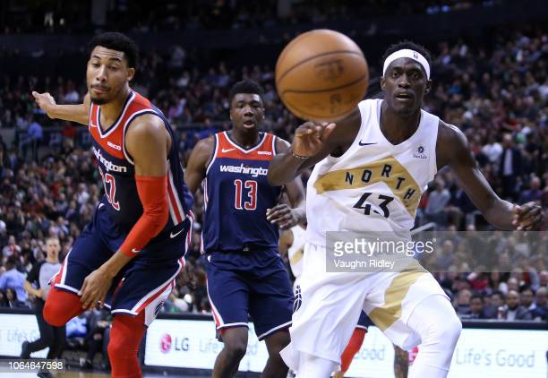 Pascal Siakam of the Toronto Raptors chases the ball as Otto Porter Jr #22 the Washington Wizards looks on during the second half of an NBA game at...