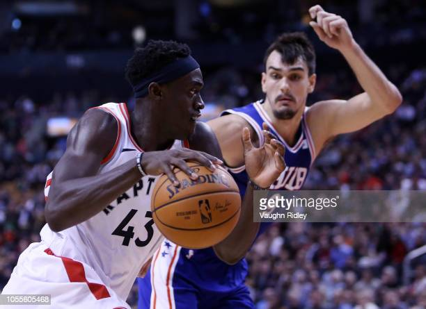 Pascal Siakam of the Toronto Raptors dribbles the ball as Dario Saric of the Philadelphia 76ers defends during the second half of an NBA game at...