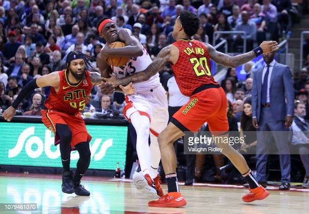 Pascal Siakam of the Toronto Raptors dribbles the ball as DeAndre' Bembry and John Collins of the Atlanta Hawks defend during the second half of an...