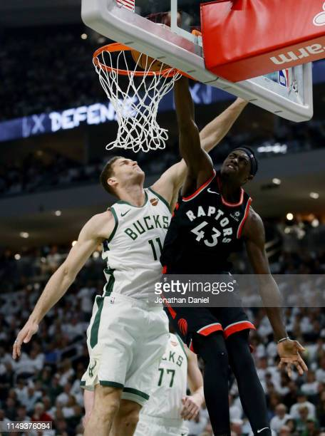 Pascal Siakam of the Toronto Raptors dunks the ball past Brook Lopez of the Milwaukee Bucks in the first quarter in Game One of the Eastern...