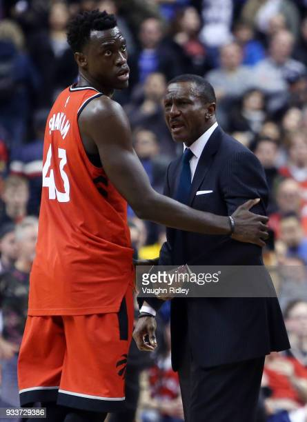 Pascal Siakam of the Toronto Raptors holds back Head Coach Dwane Casey after a call by an official during the second half of an NBA game against the...