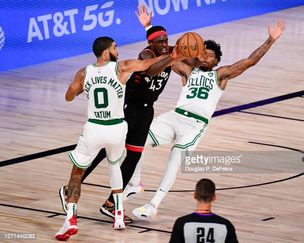 Pascal Siakam of the Toronto Raptors looks to pass the ball as Jayson Tatum and Marcus Smart of the Boston Celtics defend during the fourth quarter...