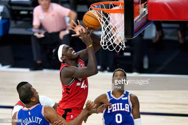Pascal Siakam of the Toronto Raptors loses control while going up for a basket against Al Horford and Josh Richardson of the Philadelphia 76ers...