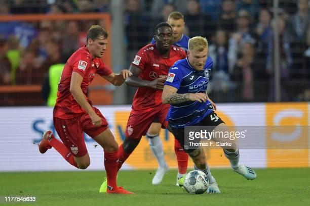 Pascal Stenzel and Orel Mangala of Stuttgart tackle Andreas Voglsammer of Bielefeld during the Second Bundesliga match between DSC Arminia Bielefeld...
