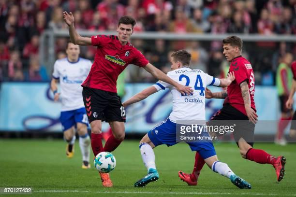 Pascal Stenzel of Freiburg is challenged by Bastian Oczipka of Schalke during the Bundesliga match between SportClub Freiburg and FC Schalke 04 at...