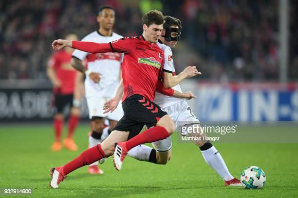 Pascal Stenzel of Freiburg is challenged by Christian Gentner of Stuttgart during the Bundesliga match between SportClub Freiburg and VfB Stuttgart...