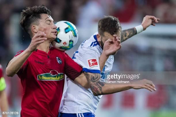 Pascal Stenzel of Freiburg jumps for a header with Guido Burgstaller of Schalke during the Bundesliga match between SportClub Freiburg and FC Schalke...