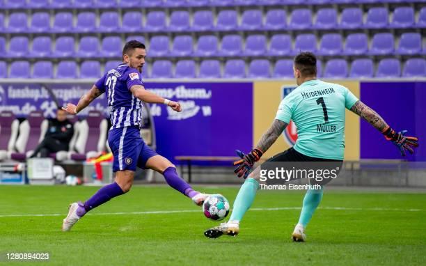 Pascal Testroet of Aue scores his team's second goal past goalkeeper Kevin Mueller of Heidenheim during the Second Bundesliga match between FC...
