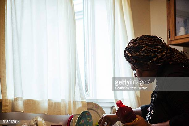 Pascaline Lisembe finds a measuring spoon for palm oil as she prepares cassava, which is one of her husband's favorite dishes at her home in...