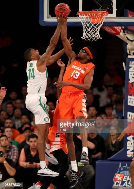Paschal Chukwu of the Syracuse Orange blocks a shot as Kenny Wooten of the Oregon Ducks heads for the net during the 2K Empire Classic at Madison...