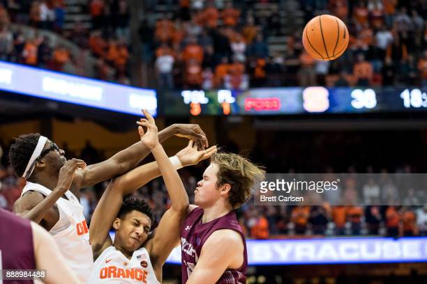 Paschal Chukwu of the Syracuse Orange makes contact with Matthew Moyer and Dana Batt of the Colgate Raiders while reaching for a rebound during the...