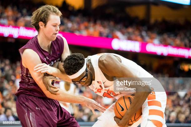 Paschal Chukwu of the Syracuse Orange pushes away Dana Batt of the Colgate Raiders while controlling the ball during the second half at the Carrier...