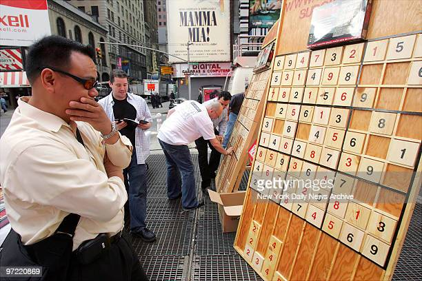 P Pascua of Fairlawn NJ works on solving a Sudoku puzzle on a gigantic board in Times Square during a nationwide competition sponsored by Sudoku...
