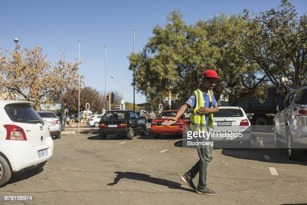 Paseka Selemela a former worker at the Savuka mine guides cars into parking spaces in an area just off Gold Street in Carletonville South Africa on...