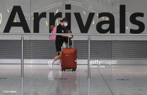 Pasenger pulls her roller suitcase on arrival in Terminal 5 at Heathrow airport in London, on June 3, 2021. - Health Secretary Matt Hancock has said...
