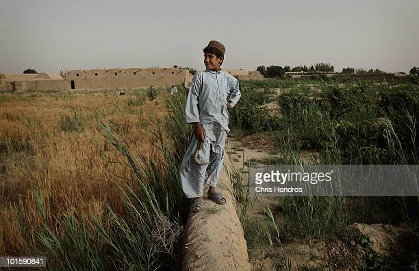 Pashtun boy stands on a mud wall in his family's farm fields June 3 2010 in Walakhan a village south of Kandahar Afghanistan Tiny Walakhan which has...