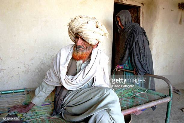 A Pashtun elder and his wife wait out a search of their house compound being carried out by US troops