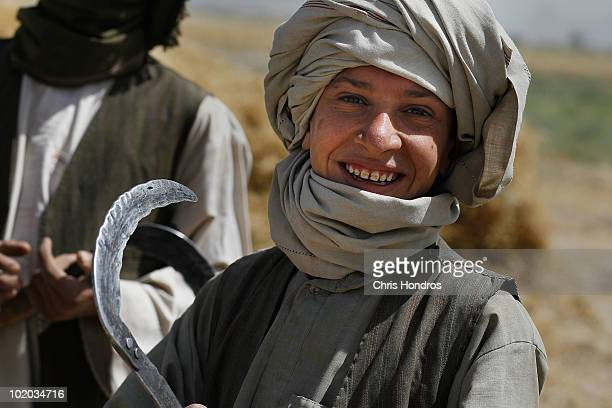 Pashtun farming boy holds his scythe as he takes a break from harvesting wheat in rural Dand District just south of Kandahar Afghanistan US soldiers...
