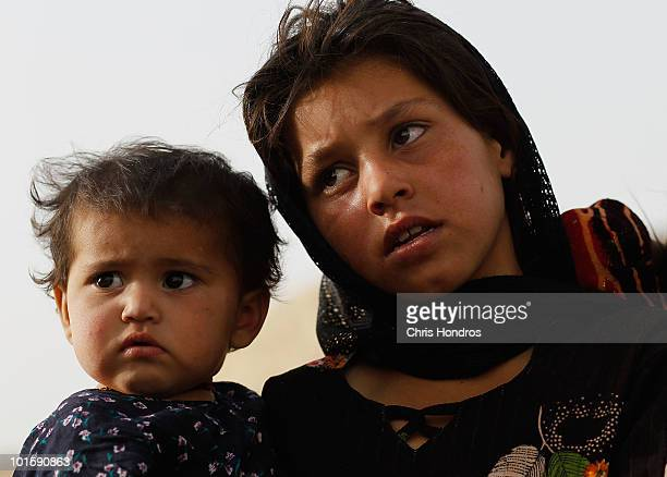 Pashtun girl holds a child while watching a US Army patrol June 3 2010 in Walakhan a village south of Kandahar Afghanistan Tiny Walakhan which has...