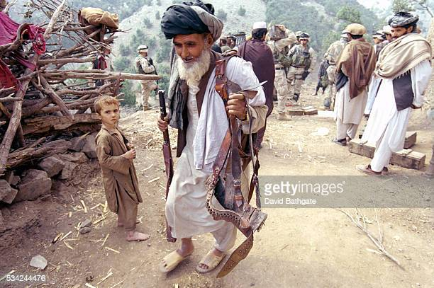Pashtun man returns home with firearms he is permitted to keep following a village search by U.S. Army soldiers.