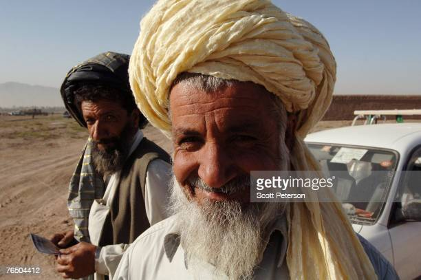 Pashtun man smiles as his car is checked as the Afghan National Police backed up by US Army's 82nd Airborne Division search for unauthorized weapons...