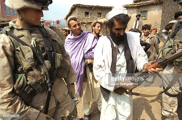 A Pashtun villager reveals his personal firearm to US troops