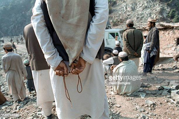 Pashtun villagers watch as US Army troops arrive to conduct a search