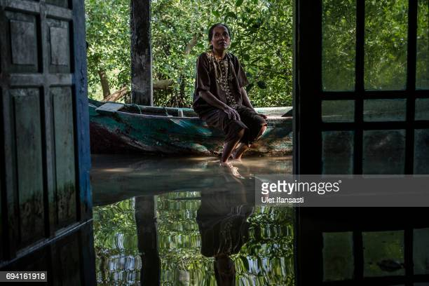 Pasijah sits inside her house submerged by rising sea levels at Bedono village on June 7 2017 in Demak Indonesia Pasijah with her family has been...