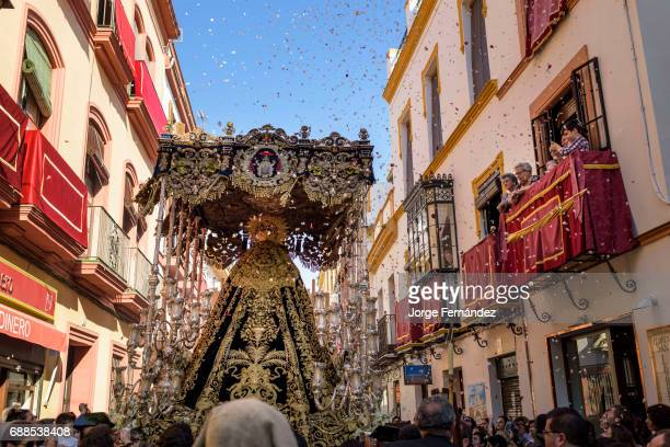 Paso of the virgin Mary being carried through the streets of Seville while people trow flowers during an Easter procession