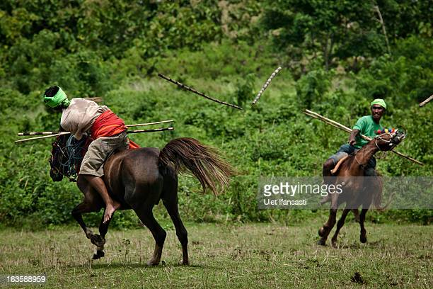 Pasola rider throwing their spear during the pasola war festival at Weiha village on March 6 2013 in Sumba Island East Nusa Tenggara Indonesia...