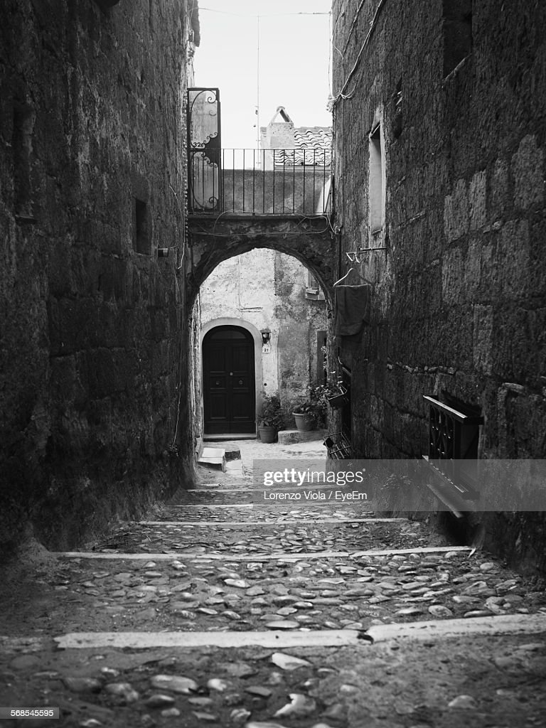 Passage Leading Towards Arch Amidst Houses : Stock Photo