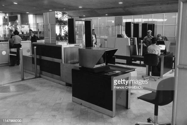 Passager passant dans les détecteurs de métaux lors du contrôle de sécurité dans l'aéroport de Roissy, en février 1988, France.