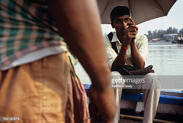 Passangers aboard a small boat cross the river Ganges on October 15 2009 in Bakkhali India The Ganges River originating in Nepal and stretching...