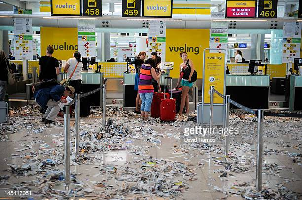 Passangers check in their luggage at the checkin desks among rubbish and paper as Barcelona Airport cleaning staff protest against budget cuts at the...