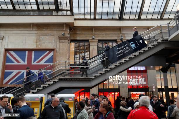 Passangers wait for an Eurostar train at the Gare du Nord railway station in Paris on October 18 after traffic through the Channel tunnel between...
