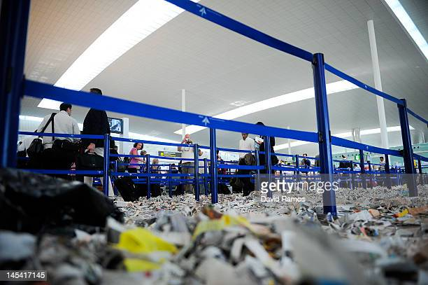 Passangers walk the security check lines among rubbish and papers as Barcelona Airport cleaning staff protest against budget cuts at the El Prat...