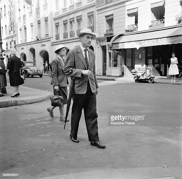 Passant muni d'un parapluie et coiffé d'un chapeau de paille dans les rues de Paris France le 8 juin 1960